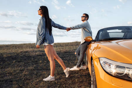 Trendy young couple staying beside a yellow convertible car. Freedom, travel and love concept. Foto de archivo