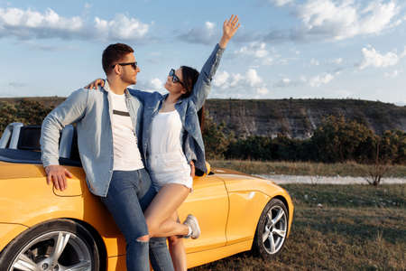 Happy young couple staying beside a yellow convertible car. Freedom, travel and love concept.