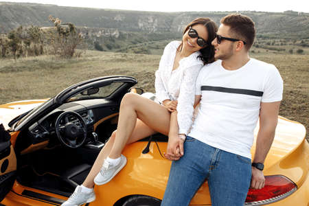 Trendy young couple have fun on convertible car. Freedom, travel and love concept.