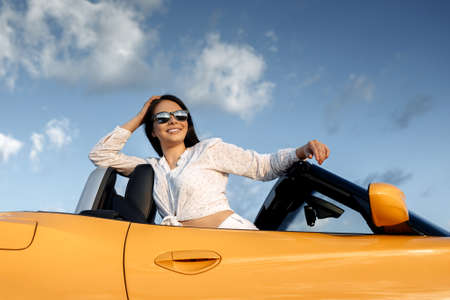 Attractive young woman sitting in yellow convertible car. Freedom, travel and careless concept.