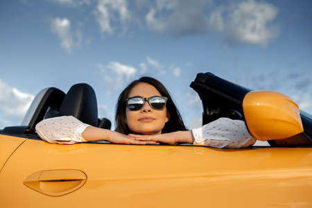 Pretty young woman sitting in yellow convertible car. Freedom, travel and careless concept.