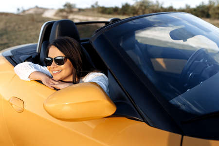 Romantic young woman sitting in yellow convertible car. Freedom, travel and careless concept. Foto de archivo