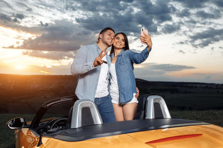 Preety young couple going on a long drive in a convertible car. Couple use smartphone for selfie.