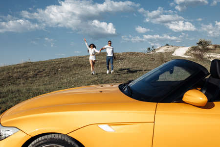 Gorgeous young couple running to a convertible car. Freedom, travel and love concept. Foto de archivo