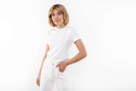 Pretty young blonde woman in casual white outfit posing over white background.