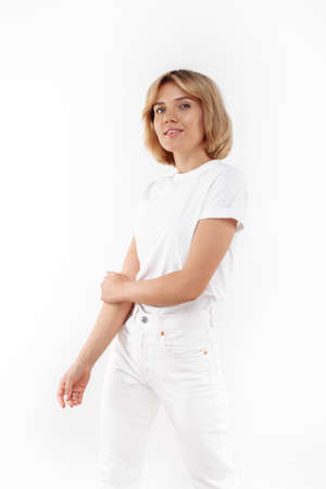 Beautiful young blonde woman in casual white outfit posing over white background. Foto de archivo