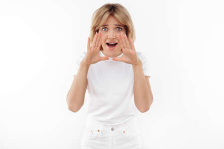 Pretty young blonde woman in casual white outfit screaming over white background. Foto de archivo