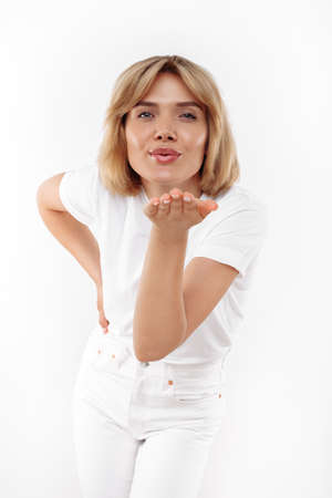 Charming young blonde woman in casual white outfit sends air kiss at the camera over white background.