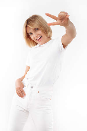 Cheerful young blonde woman in casual white outfit showing peace gesture over white background.