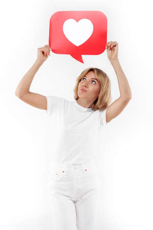 Happy young blonde woman holding speech bubble heart like symbol placard over white background. Foto de archivo