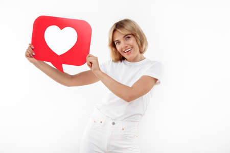 Gleeful young blonde woman holding speech bubble heart like symbol placard over red background.