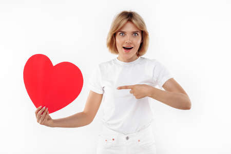 Delighted young blonde woman in casual white outfit pointing finger on paper heart over white background. Foto de archivo