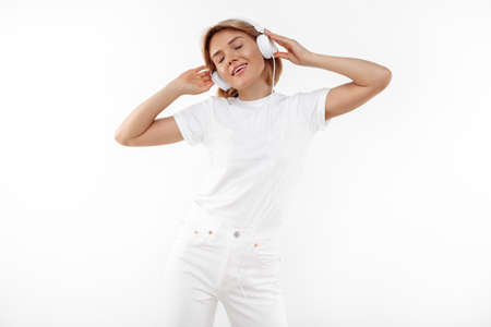 Modern young blonde woman in casual white outfit listening music in headphones over white background.