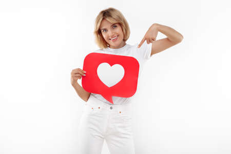 Charming young blonde woman pointing finger at speech bubble heart like symbol placard over white background. Foto de archivo