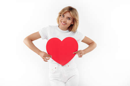 Positive young blonde woman in casual white outfit holding paper heart over white background.