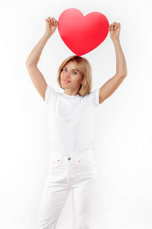 Charming young blonde woman in casual white outfit holding paper heart on the head over white background.