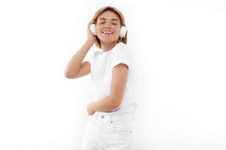 Pretty young blonde woman in casual white outfit listening music in headphones over red background.