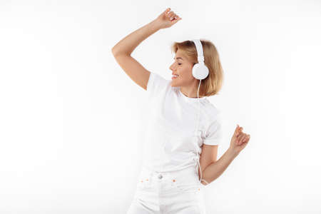 Modern young blonde woman in casual white outfit listening music in headphones over red background. Foto de archivo