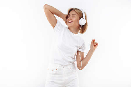 Stylish young blonde woman in casual white outfit listening music in headphones over red background. Foto de archivo