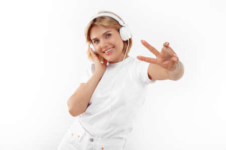 Positive young blonde woman in casual white outfit listening music in headphone over red background. Peace gesture.