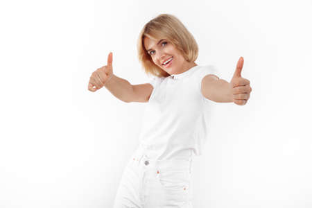 Smiling young blonde woman in casual white outfit showing thumbs up over white background.