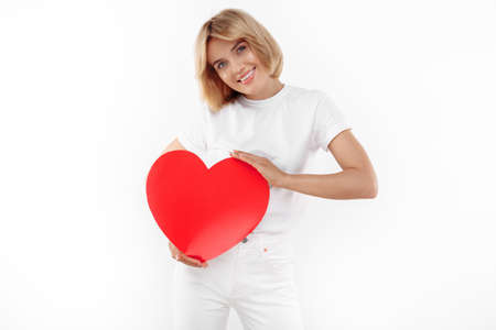 Charming young blonde woman in casual white outfit holding paper heart over white background.