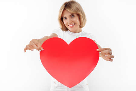 Pretty young blonde woman in casual white outfit holding big paper heart over white background.