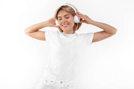 Delighted young blonde woman in casual white outfit listening music in headphones over red background.