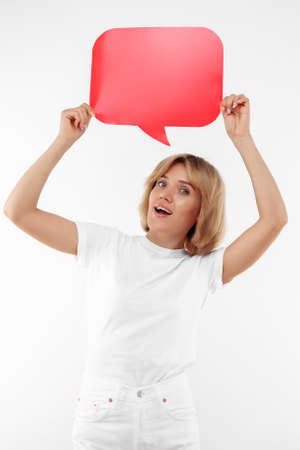 Cheerful young blonde woman holding red blank speech bubble over white background. Foto de archivo