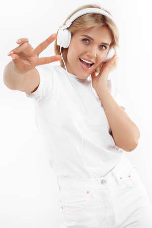 Cheerful young blonde woman in casual white outfit listening music in headphone over red background. Peace gesture.