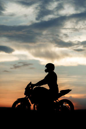 Silhouette photo of biker driving motorcycle in sunset on the on country road. Foto de archivo
