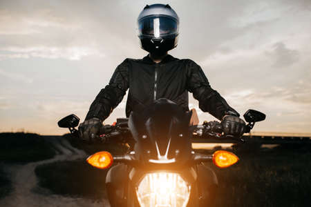 Close-up photo of biker sitting on motorcycle in sunset on the country road. Foto de archivo