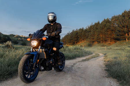 Photo of biker driving motorcycle in sunset on the country road.