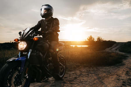 Close-up photo of biker sitting on motorcycle in sunset on the country road. Copy space.