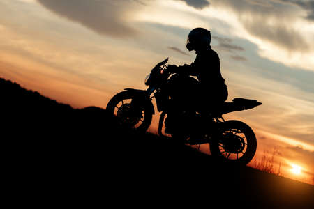 Silhouette photo of biker driving motorcycle in sunset on the on mountainous road. Success and victory concept. Foto de archivo