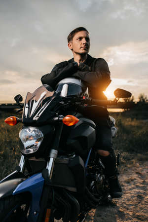 Close-up photo of handsome biker sitting on motorcycle in sunset on the country road. Foto de archivo
