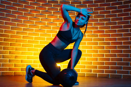 Sporty young brunette woman resting after functional exercises with medicine ball in gym in neon lights.