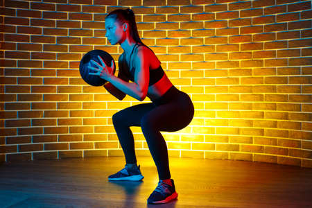 Fit young brunette woman doing squat exercise with medicine ball in gym in neon lights.