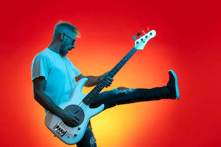 Screaming hipster man play white bass guitar in neon lights. Rock music concept.