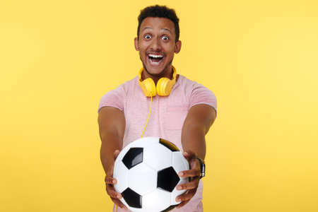 Astonished african american young man holding soccer ball with happy face over yellow background. Looking to camera. 版權商用圖片