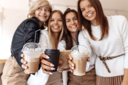 Cheerful four young women friends having coffee break while relaxing at the cafe indoors. Focus on cups. Stockfoto