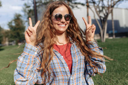 Positive young blonde hipster woman student with backpack looking to camera with happy face. Peace gesture. Stock fotó