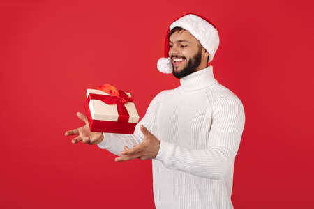 Funny hipster man wears santa claus hat cathing flying gift box over red background. Christmas and New Year concept.