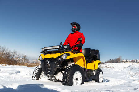 Young man driver on the ATV quad bike stand in heavy snow with deep wheel track. Moto winter sports.