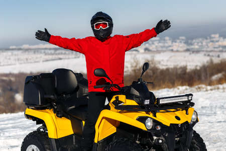 Young man driver posing on the ATV quad bike stand in heavy snow with deep wheel track. Moto winter sports. Reklamní fotografie