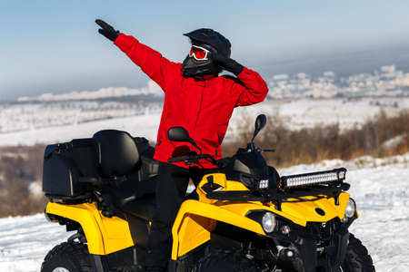 Young man driver dabbing on the ATV quad bike stand in heavy snow with deep wheel track. Moto winter sports.