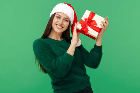 Gleeful young brunette woman wear santa claus hat and green pullover holding gift box over green background.