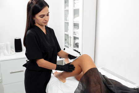 Cosmetologist make hair remove procedure on the woman leg in cosmetology cabinet.