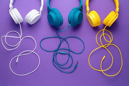 Set of three headphones over purple background. Music concept.