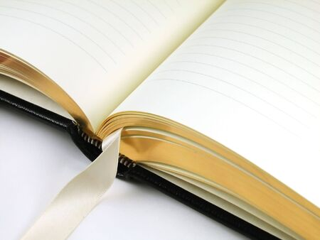 Close-up shot of a blank journal with lines to write upon and a silk bookmark bound with fine black leather and gilded page edges